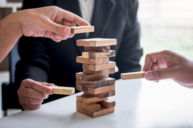 Hand of business team cooperative gambling placing making wooden block hierarchy on the tower