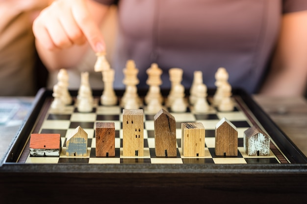 Hand of business woman moving chess to building and house models in chess game,