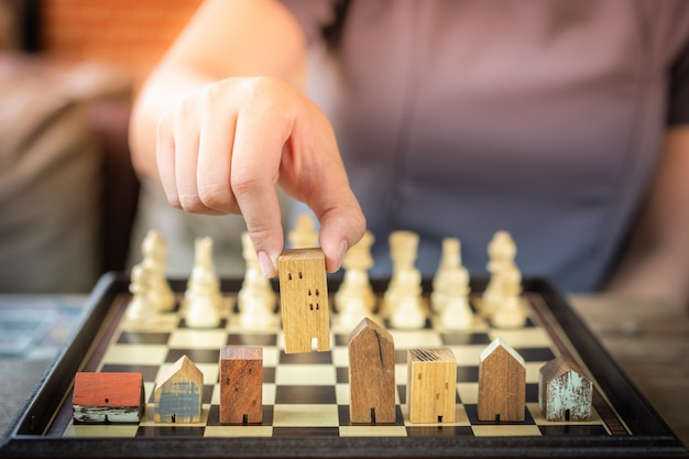Hand of business woman moving chess to building and house models in chess game