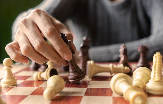 Hand of business woman playing chess for game in competition success