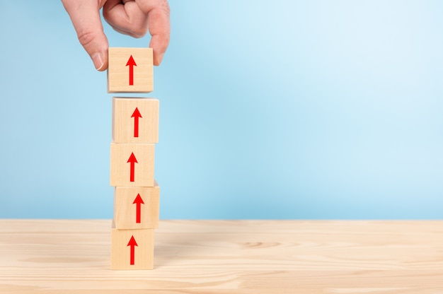 Hand of businessman arranging wooden blocks stacking with red arrow up on table, blue background