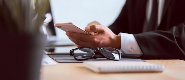 Hand of businessman in a black suit using smartphone on wooden table with typing message to contact customer and eye glasses.