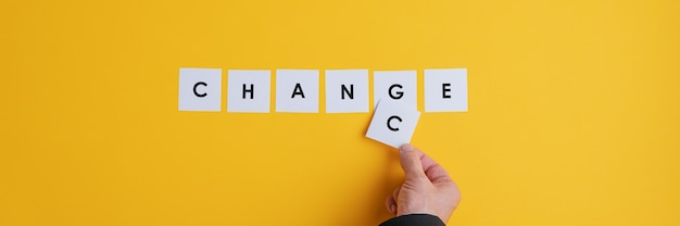 Hand of a businessman changing the word change into chance.