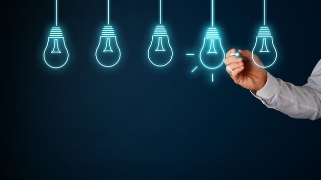 Hand of a businessman drawing light bulbs on virtual interface with glowing stylus pen with one of the bulbs lit up in a conceptual image. over blue background with copy space.