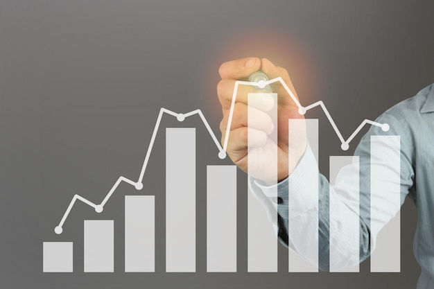 Hand of a businessman holding a pen point to top bar graph.