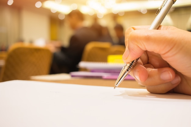 Hand businessman holding silver pen to taking notes on white paperwork or document at conf