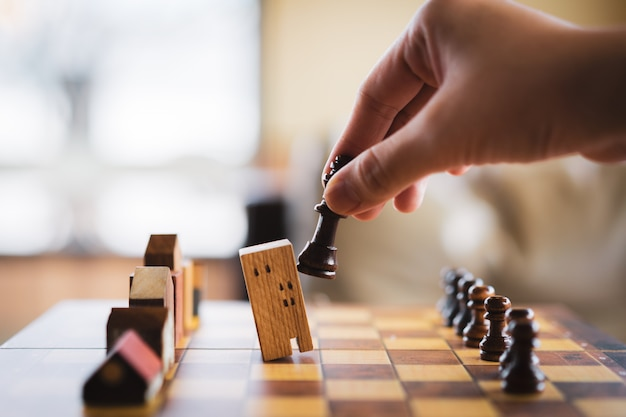 Hand of businessman moving building and house models in chess game, competition success pl