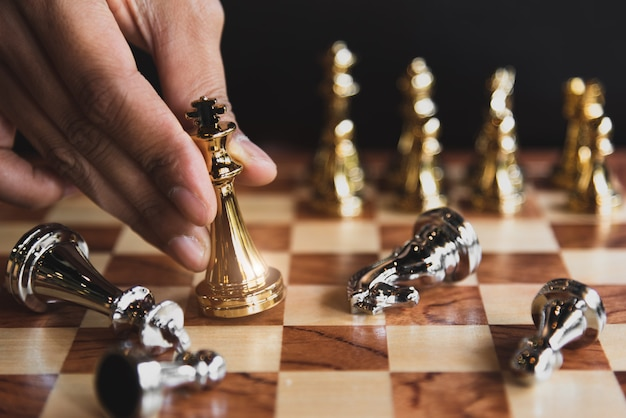 Hand of businessman moving chess for eliminating in battle competition with successful end