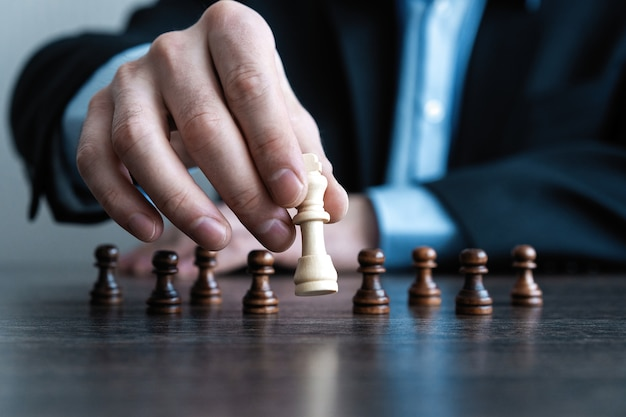 Hand of businessman moving chess figure in competition success play Premium Photo