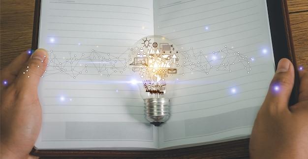 Рука бизнесмена открытая тетрадь для новой идеи лампочки с символом дела