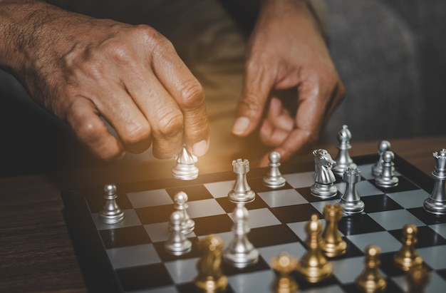 Hand of businessman playing chess assume making strategy management