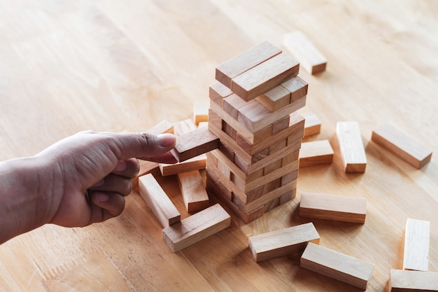 Hand businessman playing game of wooden block. business concept idea