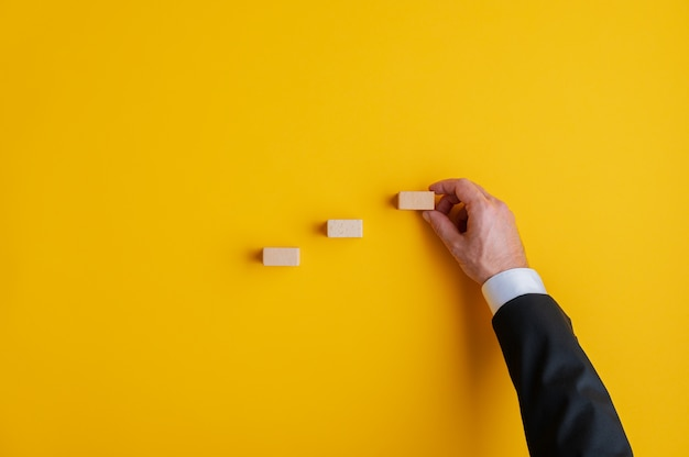 Hand of a businessman positioning wooden blocks in a stairway like structure