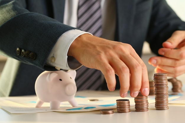 Hand businessman putting pin money into pig