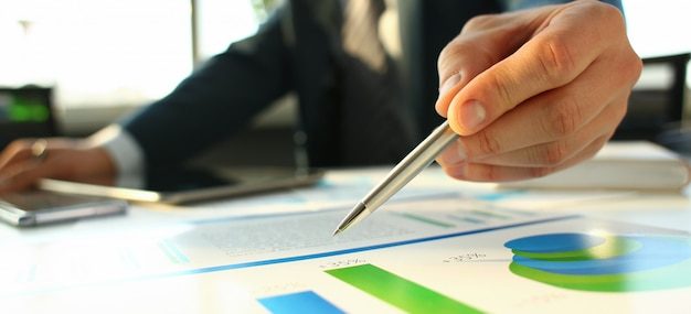 Hand of businessman in suit filling and signing with