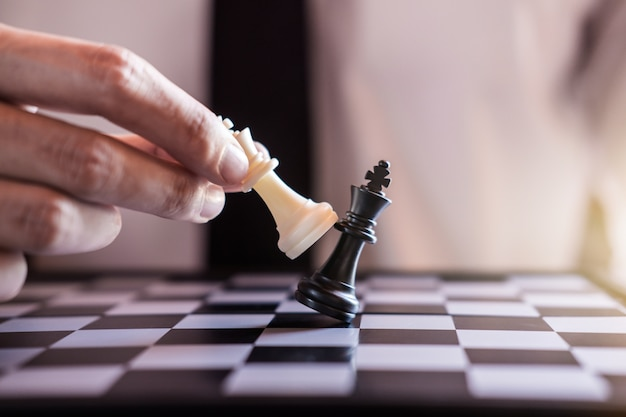Hand of businessman use king chess piece white playing game to crash overthrow the opposit