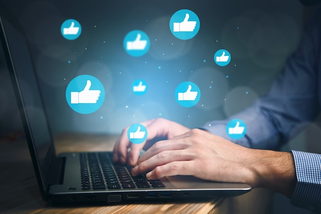 Hand of businessman using laptop with icon social media and social network. online marketing concept