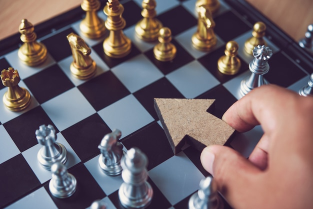 The hand of a businessman who is holding an arrow icon to point the target at strategic placement in the chess table - a guiding concept in business.