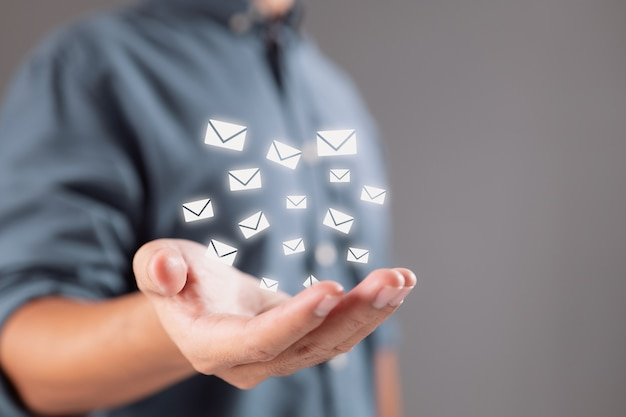 Hand of a businessman with an email icon contact us through email to receive our newsletter