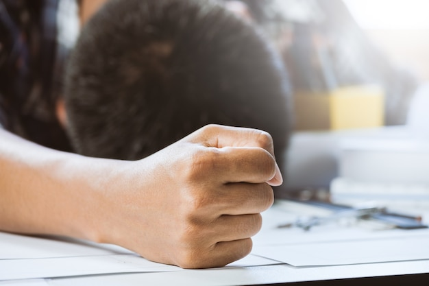 Hand businessperson having a nap on desk in workspace