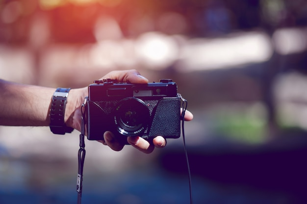 Hand and camera of the photographer travel in the mountains and nature concept photographer