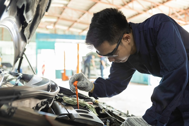 Hand of car mechanic check engine oil for maintenance in garage service car.