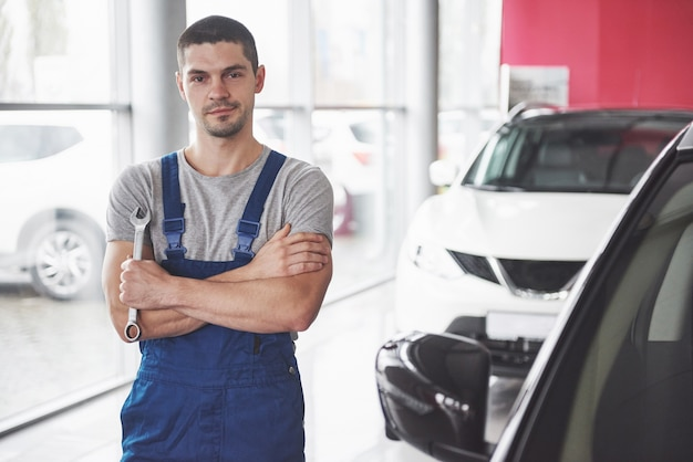 Hand of car mechanic with wrench. auto repair garage.