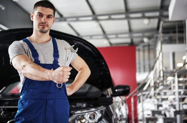 Mano del meccanico di automobili con la chiave. garage per riparazioni auto.