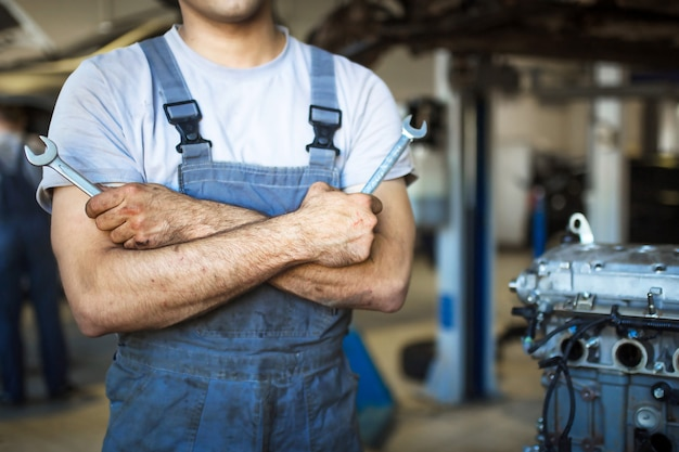 The hand of a car repairman with keys and a special tool on the background of the service area. a mechanic in a car service station in uniform. copy space