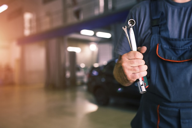 The hand of a car repairman with keys and a special tool