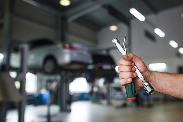 The hand of a car repairman with special tool on the service area.