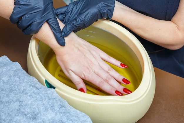 Hand care with hot wax, covering with wax, manicure salon.