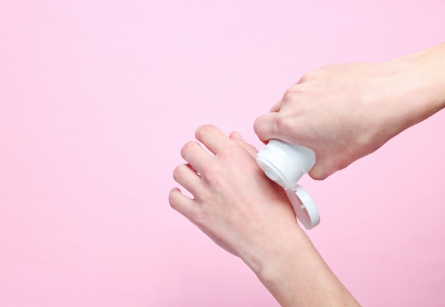 Hand care. woman holding cream tube and applying moisturizer cream on her beautiful hands for soft hand skin on pink pastel background.