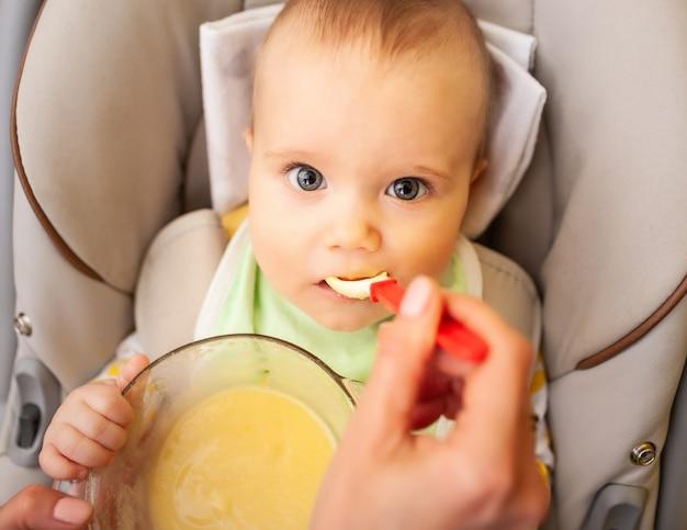 手は慎重にかわいい健康な新生児の女の子に離乳食を与えます