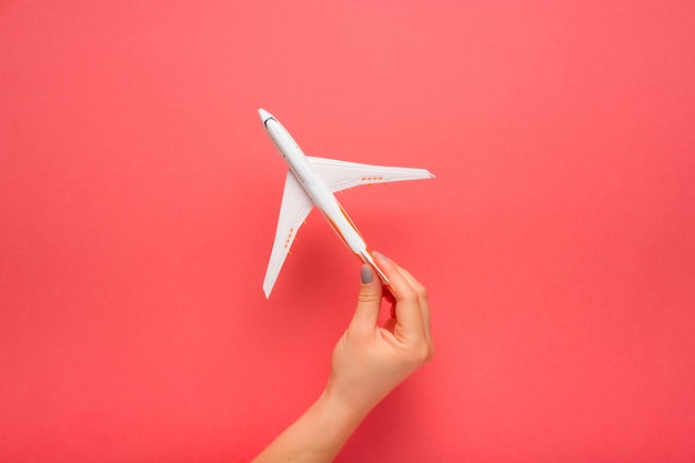 Hand carefully holding model plane. airplane on pink color background.