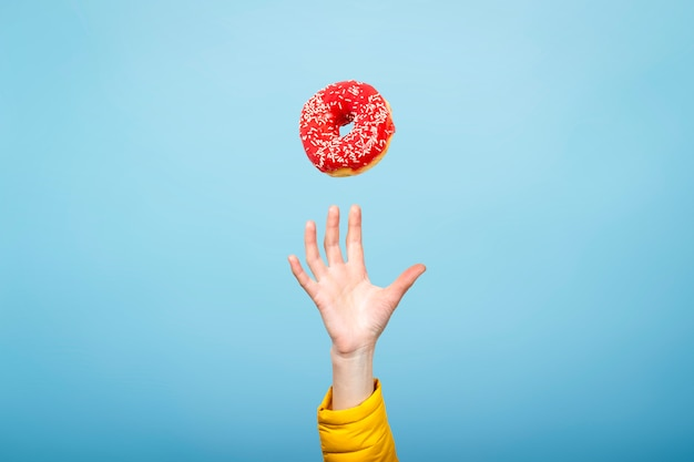 Hand catch a donut with red icing. concept of baking, handmade. flat lay, top view