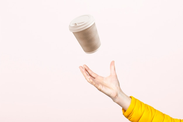 Рука ловит картонную чашку в воздухе