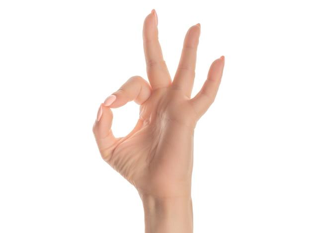 指で大丈夫シンボルを行う承認式を身振りで示す孤立した白い背景の上に指を示す手の白人の若い女性。白い背景に対して身振りで示す手のクローズアップ