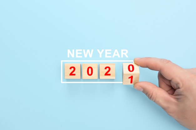Hand change wood cubes new year 2020 to 2021. new year concept.