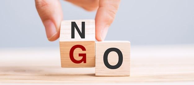 Hand change wooden cube block between no and go