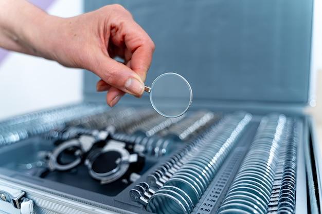 Рука меняет линзы фороптера пробной оправы. линзы из набора корректирующих линз. набор очков для проверки зрения. концепция офтальмологии.