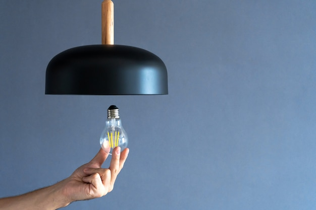 Hand changes a light bulb from a stylish lamp