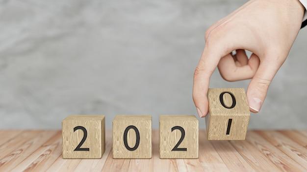 手は木製の立方体を2020年から2021年に変更します。明けましておめでとうございます2021年。3dレンダリング。