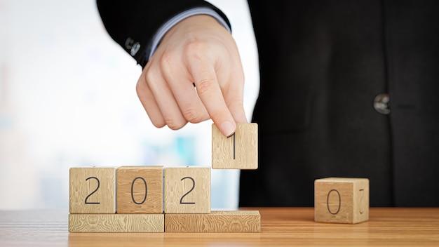 Рука меняет деревянный куб с 2020 на 2021 год. с новым 2021 годом. 3d-рендеринг.