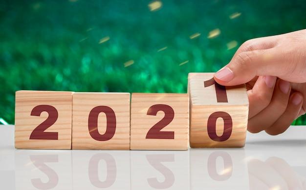 Рука меняет деревянный куб с 2020 на 2021 год. с новым 2021 годом.