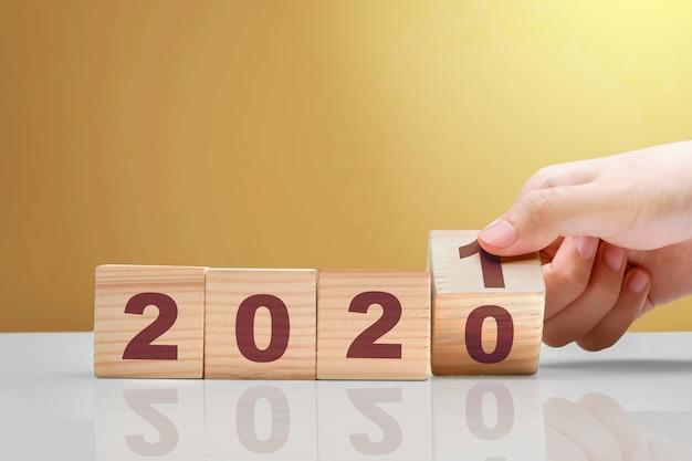 Рука меняет деревянный куб с 2020 на 2021 год