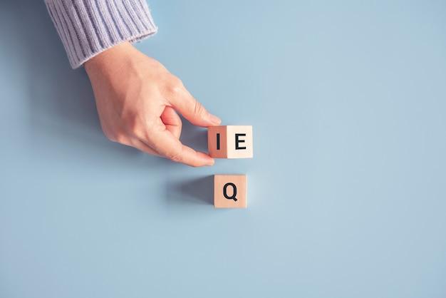 Рука меняет деревянный куб с выражения «iq» (коэффициент интеллекта) на «eq» (коэффициент эмоционального интеллекта).