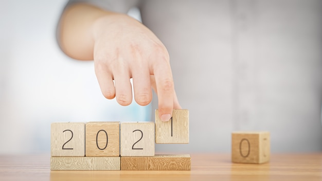 Hand changes the wooden cube from 2020 to 2021. happy new year 2021. 3d rendering.