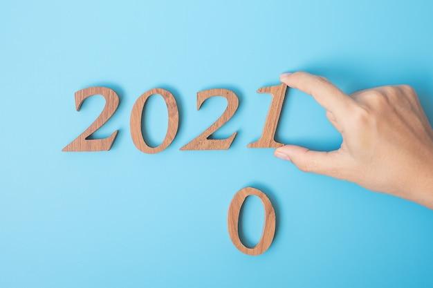 Рука меняет старый год на новый с деревянными цифрами