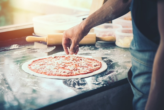 Hand chef preparing spread white cheese on pizza on marble table